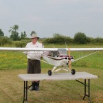 Peter Conquergood holding Piper Supercub on the judges table for static score