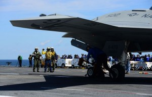 Sailors aboard the aircraft carrier USS George H.W. Bush (CVN 77) remove the chocks from an X-47B Unmanned Combat Air System (UCAS) demonstrator aircraft. George H.W. Bush is the first aircraft carrier to successfully catapult launch an unmanned aircraft from its flight deck. (U.S. Navy photo by Mass Communication Specialist 3rd Class Kevin J. Steinberg/Released)
