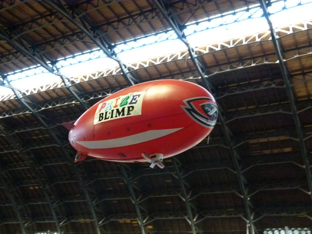 "Terry Nitsch brought the ""Prize Blimp"" all the way from Columbus, OH.  The blimp flew regular sorties all weekend, dropping prize certificates, cash and other goodies.  Here you can see the extremely high ceiling in the 100 year old Armory building."