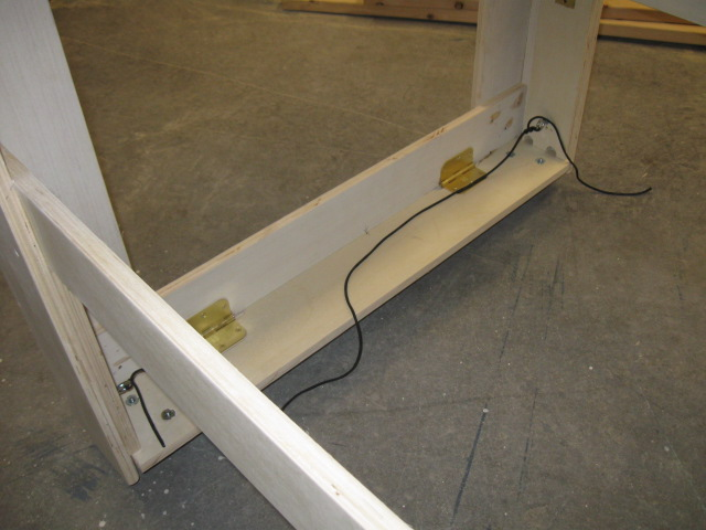 Hinged side stops pulled out and legs on the concrete floor. Rope holds the side stops out of the way.