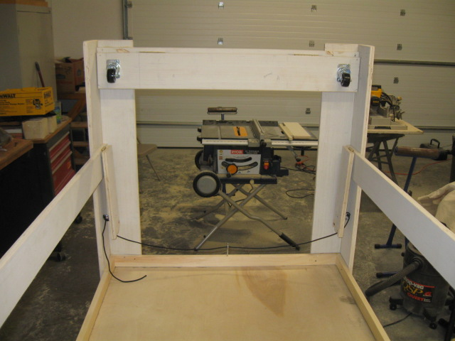 "Wheels in the retracted position. Also seen are the hinged side stops (dropped) that keep the wheels in the extended position. Note the portable 10"" table saw which handled the plywood ripping job well."