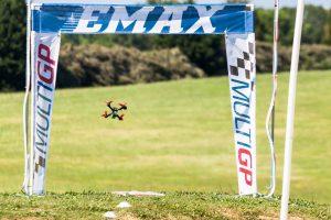 An quad blazes through a gate on the FPV course.