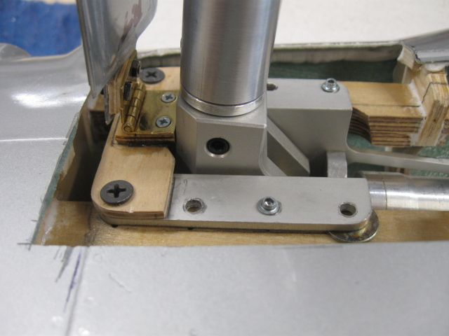 "Tight shot of the outer door hinge during preliminary assembly. By butting the brass hinge up to the base of the retract, you can be assured of being parallel and in same plane as the axis pin for the retract. The smaller plywood piece under the hinge is a height adjustment for the door to be level with the bottom of the wing. The larger plywood cross piece serves as a mount for the hinge as there is nothing there to begin with. Also note the plywood ""wedge"" under the upper half of the hinge to offset the door with the slope of the wing toward the leading edge. Note the wide cutout around the retract base. This area is closed off with lithoplate sheet later."